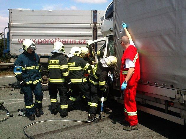 Hasiči vyprošťují zraněného řidiče nákladního automobilu z kabiny.