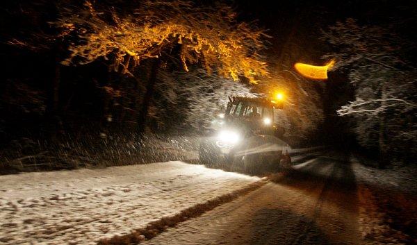 Sněhový pluh chvíli před půlnocí protahuje silnici mezi Živanicemi a Mělicemi. Silničáři byli vterénu dlouho do noci.