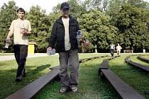 Lidé bez domova uklízejí park po skončení filmové projekce v Tyršových sadech.