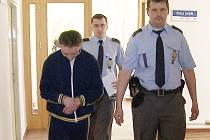 Policie eskortuje zadrženého devianta před soud.