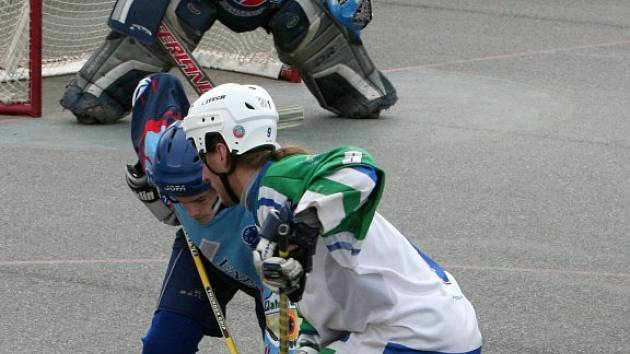 Vladimír Muchl ze Škody Plzeň (v bílém) bojuje s jedním z kladenských hráčů během utkání čtvrtfinálové série play off hokejbalové extraligy