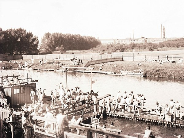 Fotografie zachycuje Městskou plovárnu vPlzni-Doudlevcích vlétě roku 1929.Tehdy tu plovárna fungovala po celou sezonu a byla oblíbeným místem rekreace mnohých Plzeňanů.