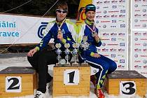 Běžci na lyžích Luděk Šeller (vlevo) a Lucie Prokešová  pózují na stupních vítězů s trofejemi, které  vybojovali  na  českém šampionátu a v  národním  poháru dorostu