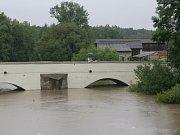 Mostní oblouky historického mostu v Dobřanech v neděli odpoledne zakryla řeka Radbuza.