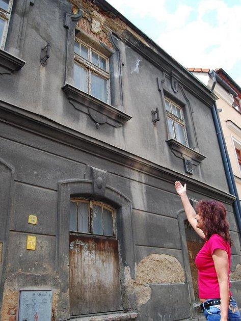 Dům, ze kterého padá zeď a omítka.