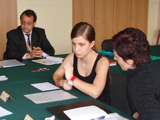Studentka 4. ročníku plaského gymnázia (druhá zprava) právě skládá zkoušku z dospělosti z českého jazyka. Vpravo je zkoušející Eva Keborová, první zleva sedí předseda maturitní komise Karel Lapský a vedle je místopředseda Ivan Varga