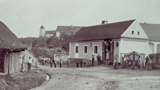 Občané Bukové na návsi ve 20. letech minulého století. V pozadí se tyčí kostel zasvěcený svatému Jiří.