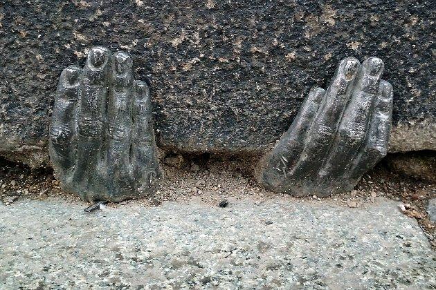 Plastika kovových lidských rukou na náměstí Republiky.