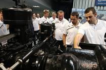 Kapitán Viktorky Pavel Horváth (druhý zprava) a trenér týmu Pavel Vrba si prohlížejí stroje ve Škodovce