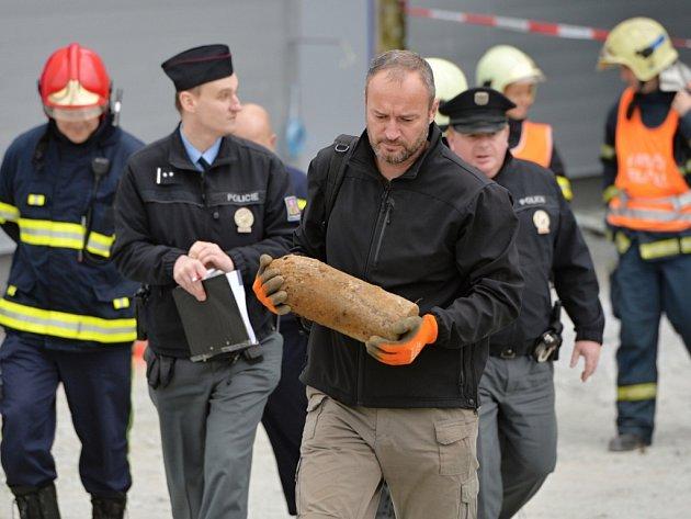 Policejní pyrotechnik odnáší cvičný dělostřelecký granát