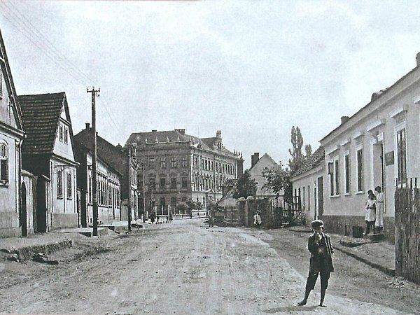 Komenského třída (dnes Masarykova) na počátku 20.století. Snímku dominuje budova nové školy zroku 1902, kterou můžeme obdivovat idnes