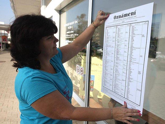 Volby sjou tady! Štěpánka Kanická vyvěšuje na budovu Úřadu městského obvodu Plzeň 4 oznámení pro občany, v kolik hodin a do které volební místnosti můžou jít volit