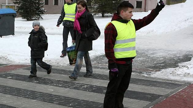 Studenti Jan Zoul (vzadu) a Tomáš Kybic (vpředu) si v pondělí poprvé samostatně vyzkoušeli úkoly dopravních asistentů. Dohlíželi na děti u 7. Základní školy v Brněnské ulici v Plzni–Vinicích