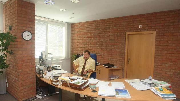 Ředitel Finančního úřadu v Plzni Roman Kasl ve své kanceláři za pracovním stolem. Zeď obložená cihlami se opakuje také v zasedací místnosti a v sekretariátu