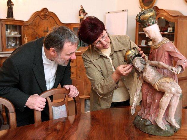 Generální vikář Plzeňské diecéze Robert Falkenauer přihlíží, jak kriminalistka Jana Prokopová nasazuje korunku na hlavu madony ze sousoší Pieta, které se našlo v Německu. Dříve měla socha ještě přírodní vlasy. O ty ovšem přišla