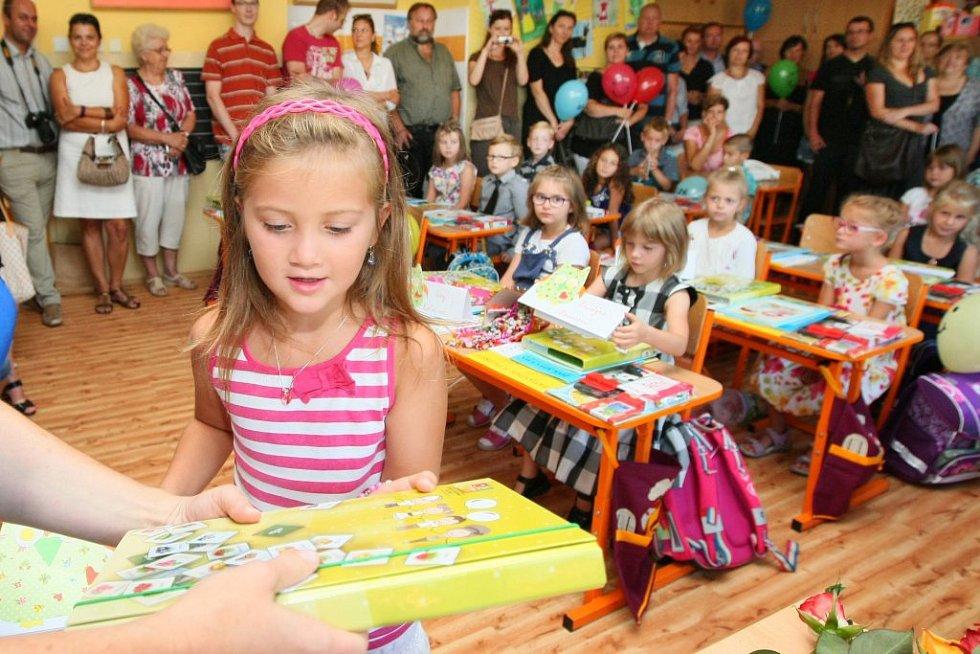 Šestadvacet dětí přivítala třídní učitelka, která každému z nich předala jmenovku a desky na sešity.