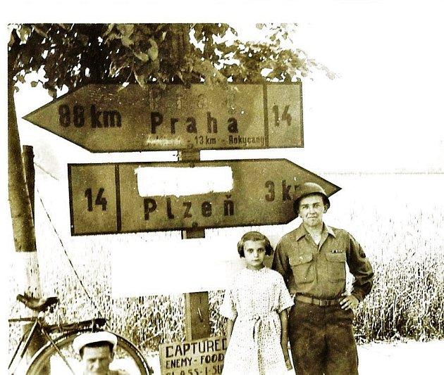 Olga Brůhová a příslušník jednotky Johna Buzzela na snímku z léta 1945. Na silničním ukazateli byly v době osvobození zamazány německé nápisy.