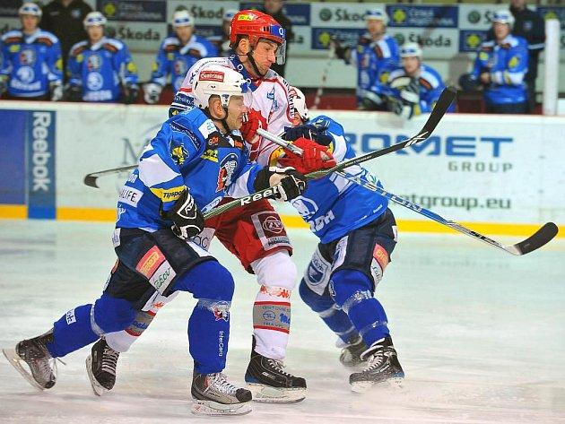 Třineckého kapitána Jana  Peterka  (v bílém)  blokuje plzeňský obránce a střelec třetího gólu Jiří Hanzlík