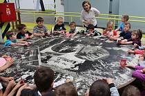 Dobrodruzi je název aktuální interaktivní výstavy o cestě emigrantů ze Stoda na Nový Zéland, která inspirovala také nadcházející příměstské tábory v DEPO2015. Snímek je ze závěru výstavy, kde děti posedí nad fotografiemi vesnice Puhoi.