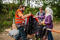 Antonín Ladman rozdává oblečení uprchlíkům. Někteří čekali na srbsko-chorvatských hranicích dlouhé hodiny v deštivém počasí.