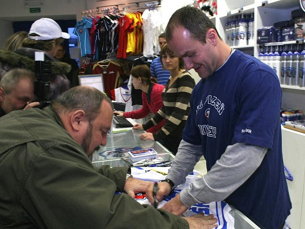 Plzeňský hokejový útočník Martin Straka (vpravo) se postavil za prodejní pult v klubovém fanshopu. O slavného prodavače byl obrovský zájem, fronta fanoušků se táhla z obchodu až ven. Straka nenabízel jen zboží, ale fanouškům se stihl i podepisovat