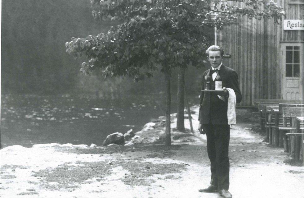 Číšník z chaty u Černého jezera (1934) je připraven obsloužit návštěvníky, kteří si mohli půjčit i jednu ze tří loděk a vydat se na projížďku po jezeře