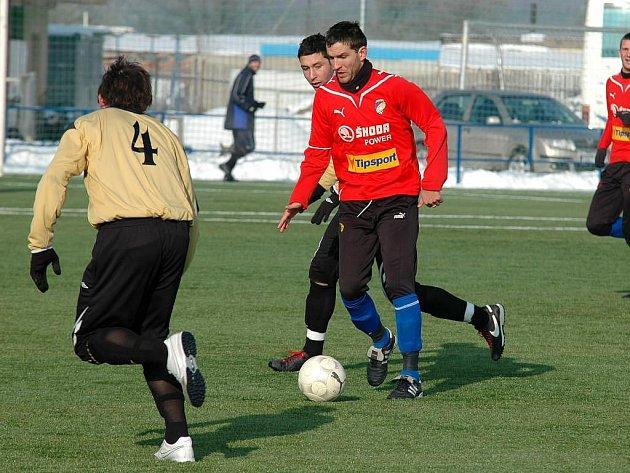 Útočník Viktorie Plzeň Marek Bakoš (u míče v červeném dresu ) se snaží přejít přes obranu soupeře ve středečním přípravném utkání s druholigovou Čáslaví