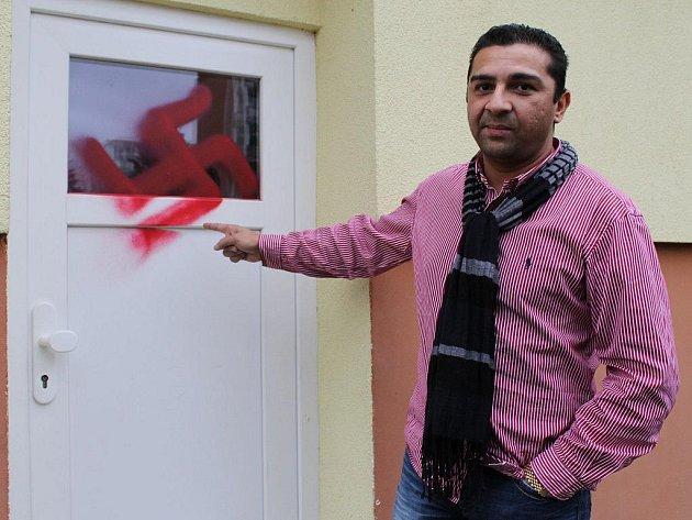 Ivan Koky před vchodovými dveřmi do domu, kde bydlí. Zatím neznámý pachatel na ně namaloval hákový kříž