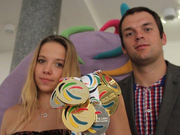 Plavkyně Tereza Polcarová se svým trenérem Patrikem Davídkem a medailemi z letošní dětské olympiády