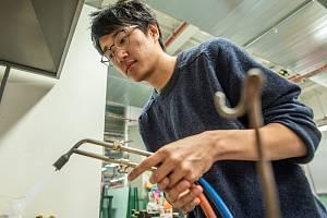 Huy Pham tepelně upravuje kov, ze kterého vyrobí šperk.