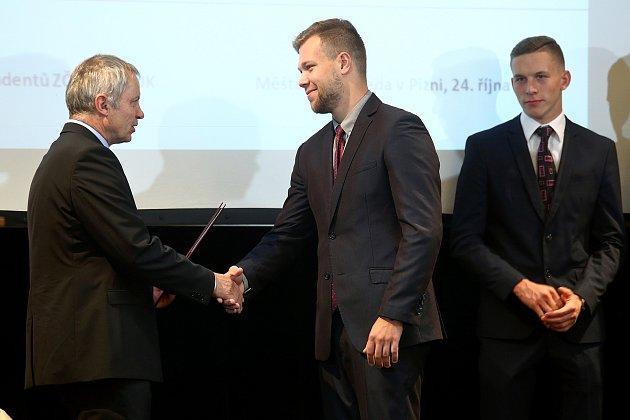 Rektor Západočeské univerzity v Plzni  Miroslav Holeček předává Petrovi Chládkovi mimořádné stipendium.