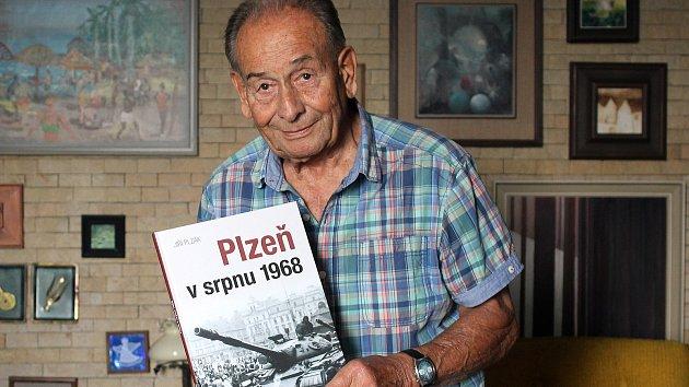 Fotograf Jiří Plzák s knihou Plzeň v srpnu 1968.