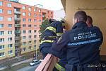 Hasiči spolu s městskými policisty zachraňovali ženu z balkonu, kde ji zamklo její dítě.