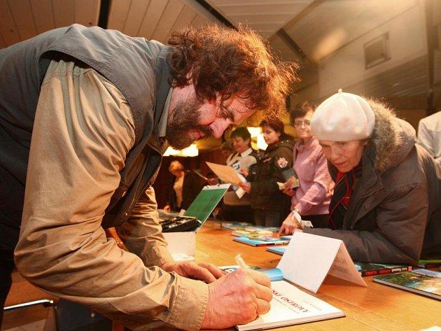 Cestovatel Leoš Šimánek podepisuje návštěvníků jeho diashow svou novou knihu.