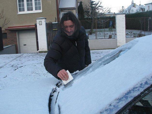 Plzeňan Antonín Kotrč smetává sníh ze svého automobilu.
