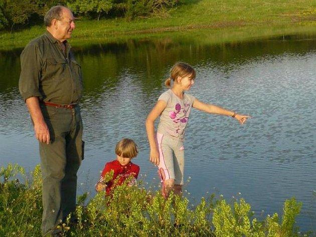 Václav Vacík s vnučkami kontroluje kvalitu vody v nově vybudovaném rybníce na ekofarmě v Roupově.