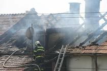 Hasiči rozebírají střechu a hasí zbytky požáru
