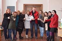 Organizátorky a podporovatelky charitního bazárku, uprostřed Markéta Čekanová (v bílém) a ředitel Diecézní charity v Plzni Jiří Lodr. Právě ženy z charitních domovů pro matky s dětmi v tísni dostanou vybraných více než 30 tisíc korun.