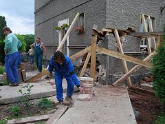 Zedníci se snaží napravit škody. Utržený roh domu podbetonují a opraví trhliny ve zdech