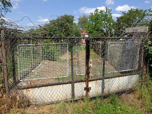 Vrata, nahoře navíc omotaná ostnatým drátem, připomínají spíše oplocení koncentračního tábora než poklidnou zahrádkářskou čtvrť s chatkami