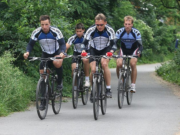 Plzeňští hokejisté (zleva) Václav Benák, Jan  Heřman, Pavel Vostřák a Jaroslav Kracík  zdolávají  kopec  od řeky Radbuzy, který ve středu  jeli  třicetkrát.
