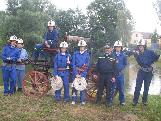 Mladí hasiči z Lochousic se shromáždili u historické stříkačky. Třetí zprava stojí strojník Silvestr Trukmüller.