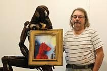 Tomáš Kůs se sochou nazvanou Patrola. Ta drží obraz Červený vlkoň.
