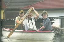 Snímek ze 17. srpna 2002. Ačkoli hladiny řek začaly klesat, v části Roudné se vytvořila laguna a voda neměla kudy odtékat. Fotografie zachycuje Helenu Ottovou, jejího manžela a jednoho ze zaměstnanců, kteří vyrazili na loďce obhlédnout obchod a dům.
