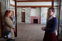 Hudební salon s krbem obloženým mramorem ukazuje návštěvníkům komenovatných prohlídek Magdalena Soukupová (vpravo).