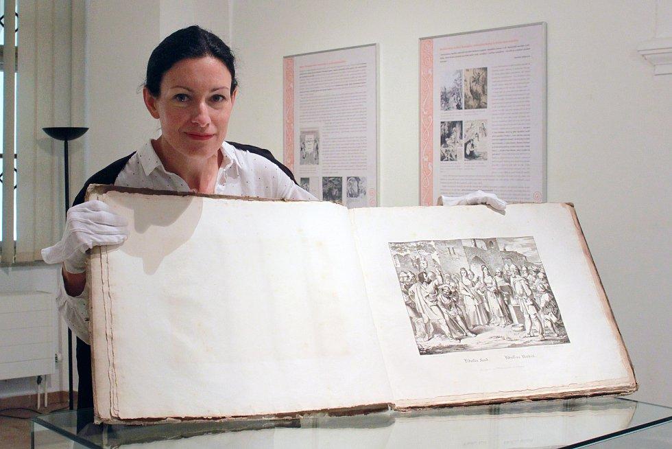 Monika Bechná z muzea v Blovicích s knihou litografií Antonína Machka z roku 1820 zapůjčenou na výstavu z fondu Studijní a vědecké knihovny.