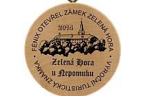 """To je ona Výroční turistická známka. Fénix otevřel zámek Zelená Hora,"""" stojí  na dřevěné plaketě vyrobené speciálně pro tři srpnové víkendy, během nichž bude jihoplzeňský zámek dominující Nepomucku mimořádně otevřen"""