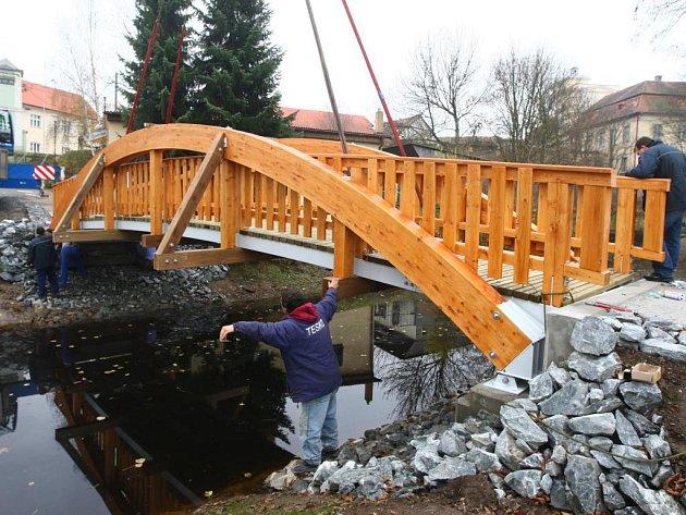 Těžká technika a šikovné ruce pomáhají ukotvit novou  dřevěnou lávku, která nahradila starou konstrukci