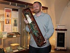 Michal Chmelenský, jeden z autorů výstavy Plzeňské kamnářství, ukazuje rohový kachel kamen, která byla v bytě Emila Škody