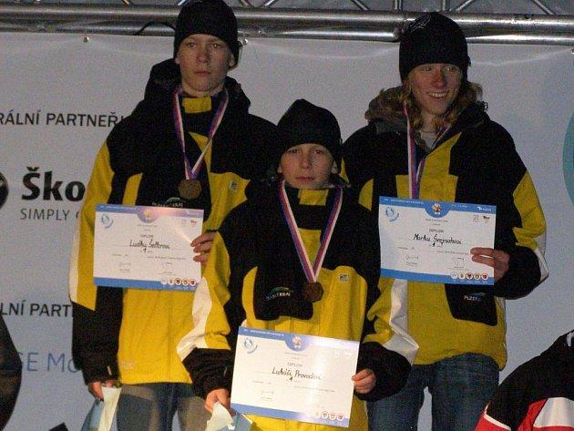 Běžci na lyžích Luděk Šeller, Lukáš Provod a Marek Švejnoha (zleva) si na nejvyšším stupínku vychutnávají vítězství v závodě štafet na zimní olympiádě dětí a mládeže.